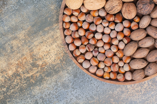 Nahrhafte gemischte braune nüsse auf holzschale. hochwertiges foto