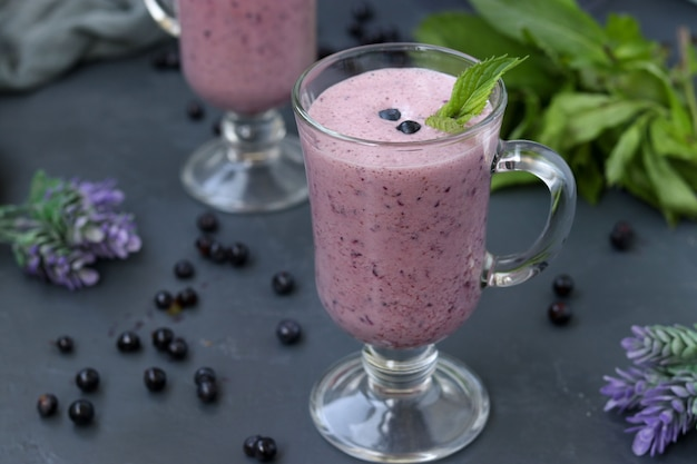 Nahrhafter cocktail mit joghurt und blaubeeren in gläsern auf einer dunklen oberfläche, gesunde ernährung