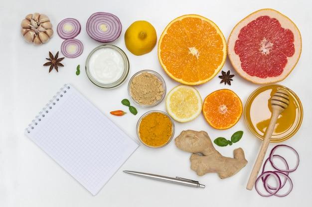 Nahrung zur stärkung der immunität und zum schutz vor viren. notizbuch und stift auf dem tisch. naturheilmittel zur grippeprävention. flach liegen Premium Fotos
