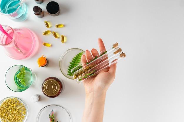 Nahrungsergänzungsmittel im labor mit pflanzenblättern zubereiten. gesundheits- und schönheitskonzept