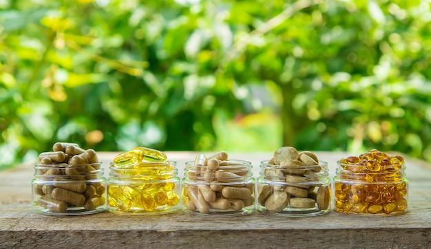 Nahrungsergänzungsmittel, vitamine und heilkräuter in gläsern auf holztisch auf verschwommenem pflanzenhintergrund