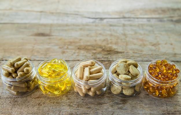 Nahrungsergänzungsmittel, vitamine und heilkräuter in gläsern auf holztisch