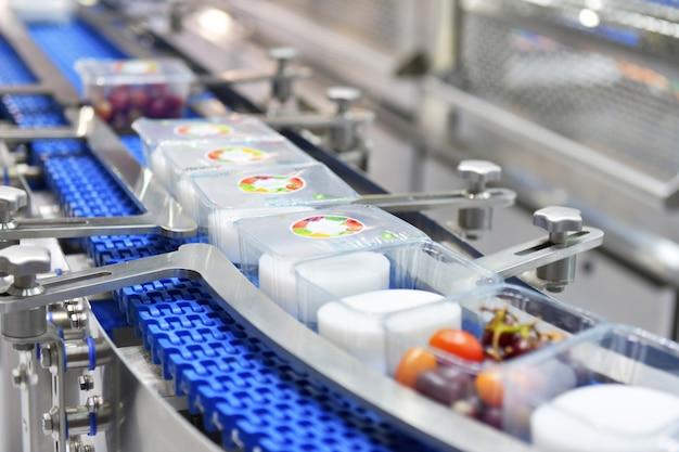 Nahrungsmittelboxen übertragen auf automatisierte fördertechnik-industrieautomation zur verpackung