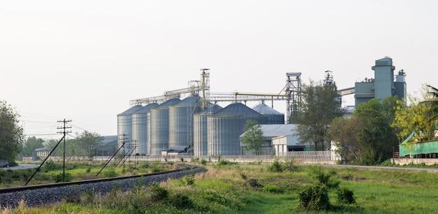 Nahrungsmittelindustriegebäude mit landwirtschaftlichen silos und eisenbahn in der stadt