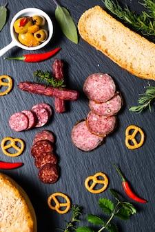 Nahrungsmittelparty mit verschiedenen arten des fleisches und des selbst gemachten brotes auf schwarzem schieferstein