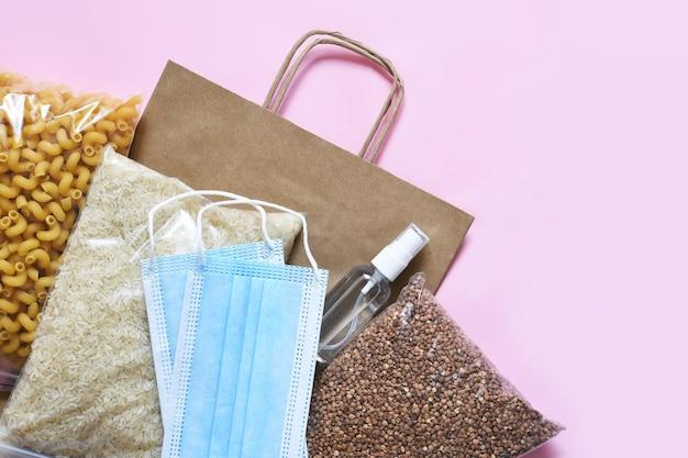 Nahrungsmittelversorgungskrise auf einem rosa hintergrund. pasta, buchweizen, maske, antiseptikum, papier. spende. flaches essen.