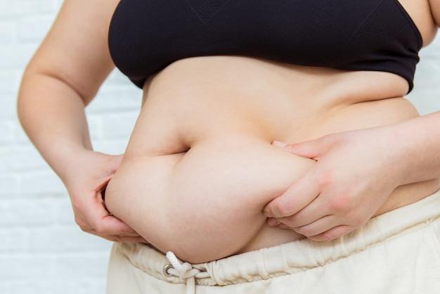 Nahrungssucht, diät, gesundheitswesen, nährwert, gewichtsverlust, gesunde ernährung, wohlbefinden. fetter ungesunder frauenkörper. bauchseiten zusammendrücken. messdame verfahren