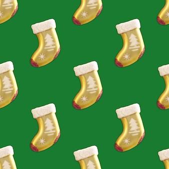 Nahtlose musterhintergrundgoldweihnachtssocke auf grünem hintergrund.