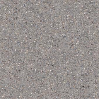 Nahtloser kippbarer betonboden mit rissen und kleinen kieselsteinen