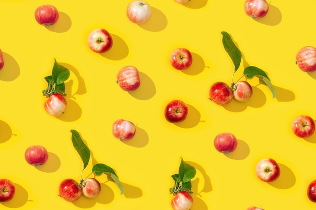 Nahtloses kreatives muster aus kleinen roten äpfeln und grünen blättern mit dunklen schatten.
