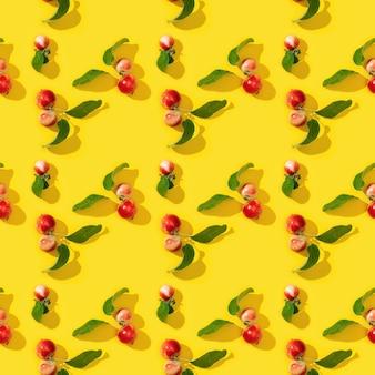 Nahtloses muster aus kleinen roten äpfeln und grünen blättern auf gelb