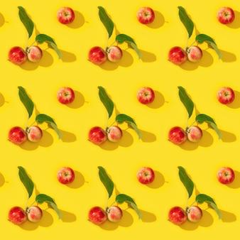 Nahtloses muster aus reifen kleinen roten äpfeln und grünen blättern auf gelb
