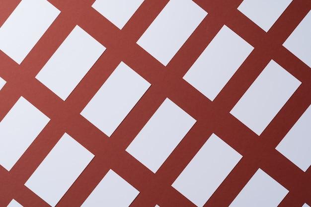 Nahtloses muster der leeren weißen visitenkarten auf burgunderpapier, draufsicht