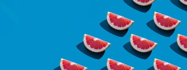 Nahtloses muster der orange grapefruit mit schatten auf blauem hintergrund mit kopienraum. banner. sommerurlaub minimales trendiges konzept. gesunde essgewohnheiten.