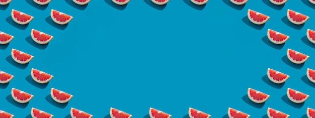 Nahtloses muster der orangefarbenen grapefruit mit schatten auf blauem hintergrund mit kopienraum. banner. sommerurlaub minimales trendiges konzept. gesunde essgewohnheiten.
