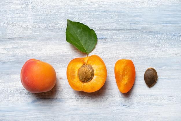 Nahtloses muster mit aprikose. aprikosenfrüchte und die hälfte auf blauer wand flach liegen. draufsicht. natürliches, grünes konzept. speicherplatz kopieren. frisch geschnittene aprikosenfruchtscheiben. kreatives layout. lebensmittelkonzept