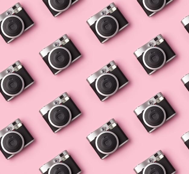 Nahtloses muster mit vintage sofortbildkamera am pastellrosa tisch.