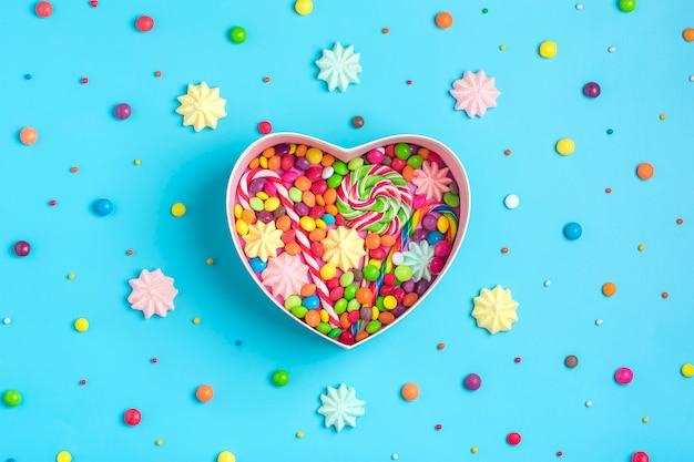 Nahtloses muster von bunten bonbons der mischung - lutscher, meringe, schokolade, besprühen, geschenkboxform des herzens, blauer hintergrund