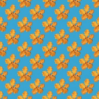 Nahtloses muster von gelben herbsteichenblättern auf blauem hintergrund, kopienraum. kann als natürlicher hintergrund, herbstdruck auf stoff, geschenkpapier, postkarte verwendet werden