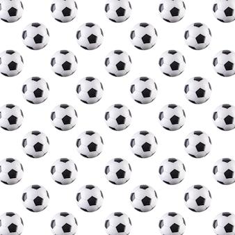 Nahtloses muster von kugeln. schwarz-weiß-fußbälle fliegen in die luft, isoliert auf weißem hintergrund. minimalistisches sportkonzept