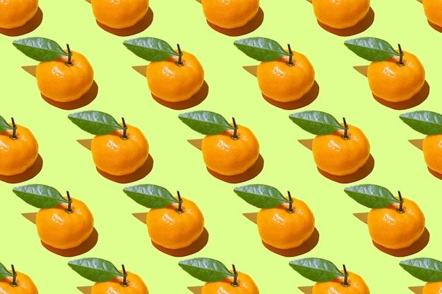 Nahtloses muster von reifen mandarinen mit grünen blättern auf einem grün