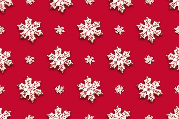 Nahtloses muster von weihnachtslebkuchen in formschneeflocken auf rotem hintergrund. weihnachtshintergrund.