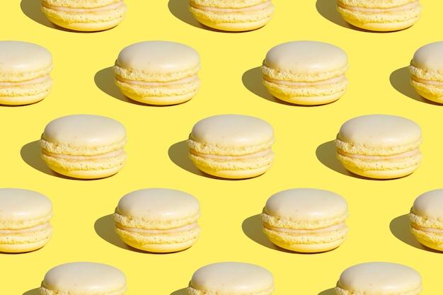 Nahtloses muster von zitronen-französischen makronendesserts mit creme auf gelb