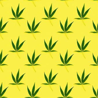Nahtloses regelmäßiges kreatives muster mit natürlichen grünen blättern der cannabispflanze.