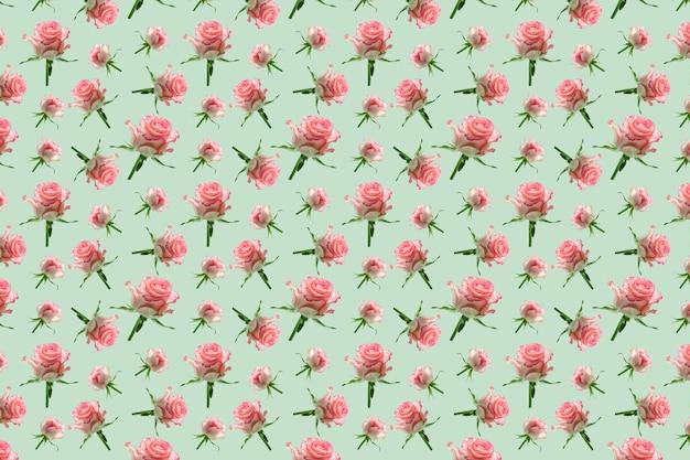 Nahtloses rosa blumenmuster der tapete auf pastellgrünem hintergrund. nahtloses rosa rosenmuster für stoff und tapete, für design und dekoration. schöne blumen.