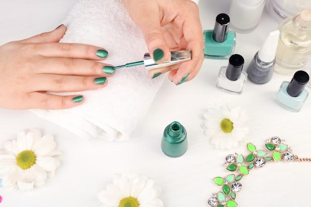 Nail art konzept. frau, die sich maniküre auf weißem tisch gibt