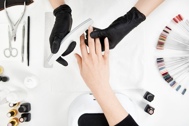 Nail tech feilenägel mit nagelfeile. professionelle maniküre-tools.
