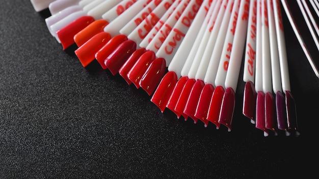 Nailart-design. satz falsche nägel für die maniküre. lackfarbpalette für die nagellackierung. künstliche nägel auf transparenter basis. fokussiert auf rote farbe
