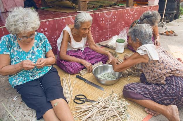 Nakhon phanom, thailand - 25. märz 2019: ältere frau der gruppe, die manuell bambus spinnt.