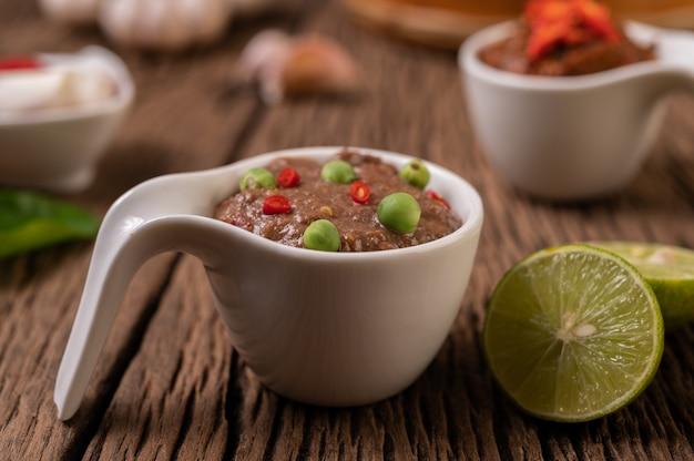 Nam phrik kapi mit chili und zitrone auf holzboden.