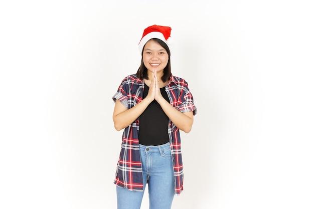 Namaste-gruß der schönen asiatischen frau mit rotem kariertem hemd und weihnachtsmütze, isoliert auf weiss