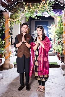 Namaste oder namaskara - indisches paar begrüßt gäste auf diwali-festival oder hochzeit