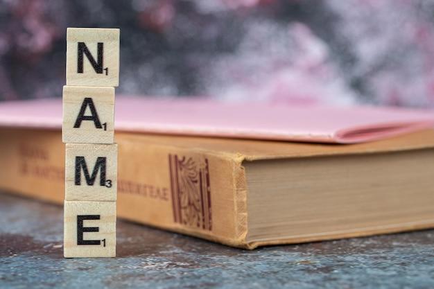 Namensschreiben mit schwarzen buchstaben auf holzwürfeln mit einem alten buch herum. hochwertiges foto