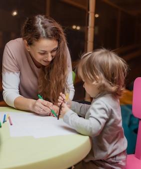 Nanny bringt einem kleinen mädchen bei, wie man mit buntstiften zeichnet, während man an einem tisch in einem kinderunterhaltungszentrum sitzt