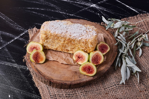 Napoelon-kuchen mit feigen und blättern auf wolltischdecke.