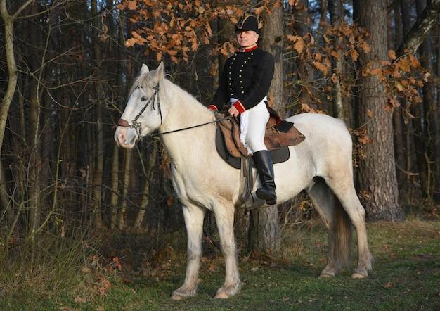 Napoleon bonaparte auf einem weißen pferd vor dem hintergrund eines herbstwaldes
