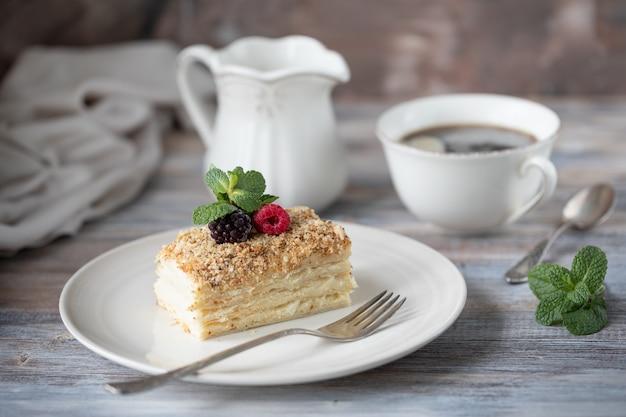 Napoleon dessert in einem teller mit beeren und minze, mit einer tasse cappuccino auf einem holztisch.