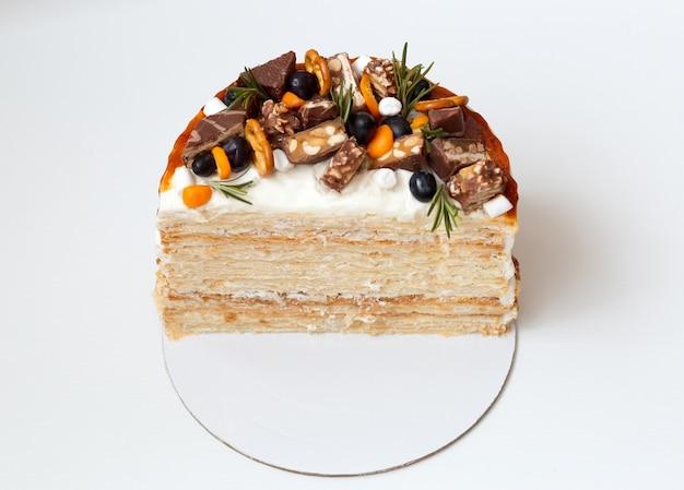 Napoleon-kuchen im schnitt, ein stück kuchen, dekoriert mit beeren, schokolade und süßigkeiten auf einer weißen oberfläche