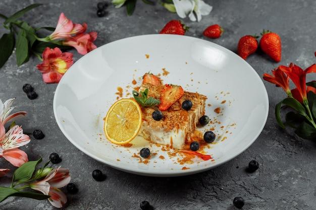 Napoleon-kuchen mit karamellsauce. zarter blätterteigkuchen mit vanillepudding und karamellsauce, dekoriert mit erdbeeren, blaubeeren und minze