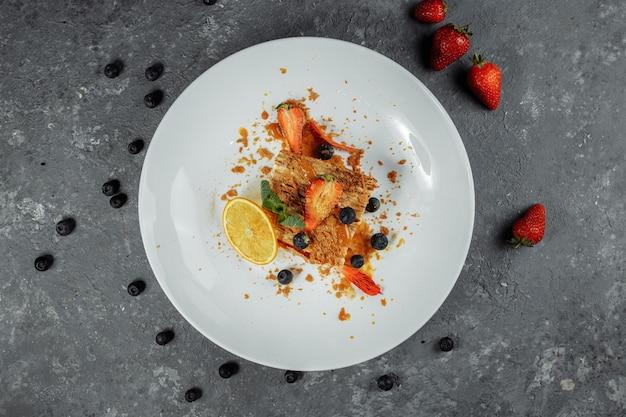 Napoleon-kuchen mit karamellsauce. zarter blätterteigkuchen mit vanillesoße und karamellsauce, dekoriert mit erdbeeren, blaubeeren und minze.