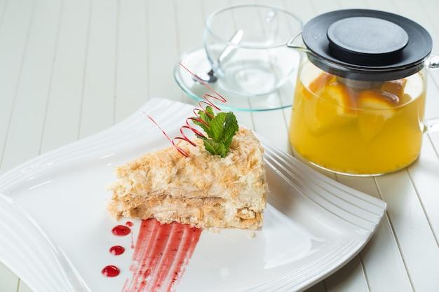 Napoleon-kuchen verziert mit einer spirale aus roter schokolade, minze und beerenmarmelade auf einem weißen teller