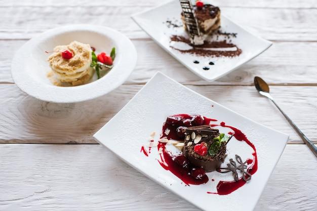 Napoleon und schokoladenkuchen mit tiramisu, die auf holztisch dienen, schließen oben