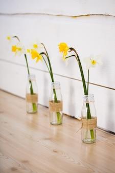 Narzissenblüten in einer vase mit wasser stehen im innenraum auf dem boden.