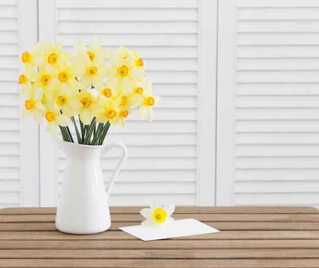Narzissenblütenköpfe auf braunem holztisch, weißer einladungskartentempate und weiße fensterläden