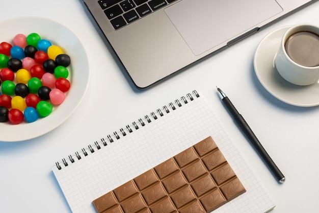 Naschen bei der arbeit, haben ein bisskonzept. laptop, süßigkeiten