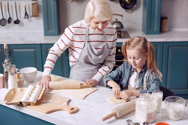 Naschkatze. entzückendes kleines mädchen, das ihrer großmutter hilft, kekse zu machen, verschiedene figuren herauszuschneiden, während die frau etwas mehr teig ausrollt